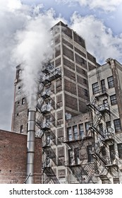 Detroit Michigan city view. There is an old building with graffiti and a fire escape along it's side. There is a steam pipe in front creating an eerie feel.