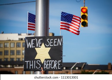 """DETROIT, MICHIGAN - JUNE 14, 2018: A sign  with American flags is held aloft, saying """"We've seen this before"""" with a Jewish yellow star at the protest to Keep Families Together in Detroit."""
