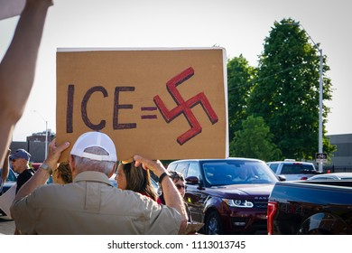 DETROIT, MICHIGAN - JUNE 14, 2018: A man holds a protest sign that equates ICE to a swastika, or the Nazi party, at the protest to Keep Families Together in Detroit.