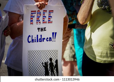 "DETROIT, MICHIGAN - JUNE 14, 2018: A protestor holds a sign that says, ""Free the Children!!!"" with an illustration of children behind a fence at the protest to Keep Families Together in Detroit."