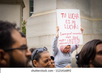 """DETROIT, MICHIGAN - JUNE 26, 2018: A woman holds a sign that says """"Your fight is my fight"""" in Spanish to protest the supreme court's ruling on the muslim ban in Detroit, MI."""