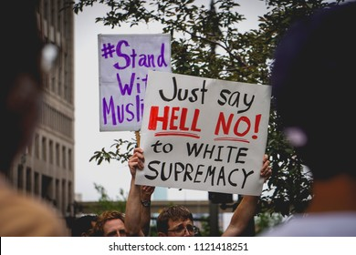 "DETROIT, MICHIGAN - JUNE 26, 2018: Protestors hold signs that say ""Just say hell no to white supremacy"" to protest the supreme court's ruling on the muslim ban in Detroit, MI."