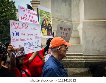 DETROIT, MICHIGAN - JUNE 26, 2018: Activists hold protest signs at a rally in Detroit against the supreme court's ruling on Trump vs. Hawaii.