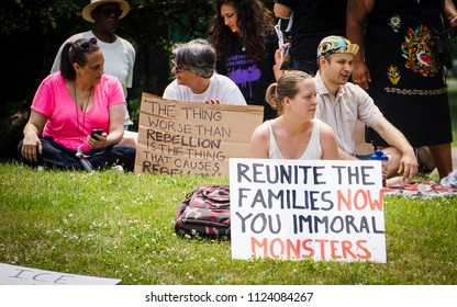 "DETROIT, MICHIGAN - JUNE 30, 2018: An activist in Detroit holds a protest sign that says ""Reunite the families now you immoral monsters."""