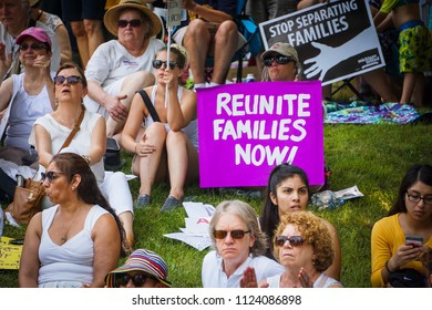 """DETROIT, MICHIGAN - JUNE 30, 2018: An activist in Detroit holds a protest sign that says """"Reunite families now!"""" among the crowd"""