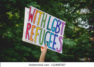 "DETROIT, MICHIGAN - JUNE 30, 2018: An activist in Detroit holds a protest sign that says ""With LGBT Refugees."""