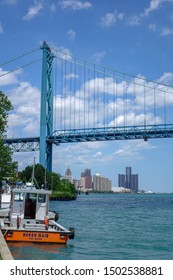 Detroit, Michigan / USA - July 9 2017: Tugboat in Detroit river with city and Ambassador bridge in background.
