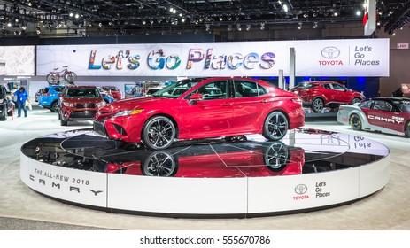 DETROIT, MI/USA - JANUARY 12, 2017: A custodian polishes a car near a 2018 Toyota Camry at the North American International Auto Show (NAIAS).