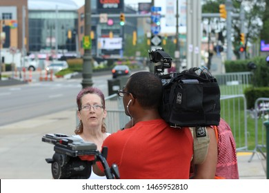 Detroit, MI/USA: July 29, 2019 – News crew interviews woman on Woodward Avenue in Detroit. Little Caesars Arena in background.