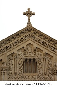 Detroit, MI/USA: Sept. 2, 2017 – Carved cross at tip of elaborately carved gable of St. Aloysius Catholic Church, built in 1932 in the Italian and French Romanesque style.
