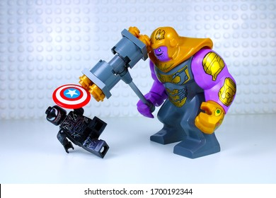 DETROIT, USA - APRIL 11, 2020: Venom versus Thanos. Lego Mini-figures. Lego Thanos hammers Venom as venom shields himself.