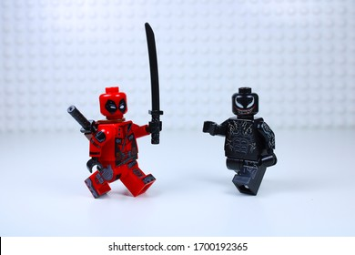 DETROIT, USA - APRIL 11, 2020: Deadpool versus Venom. Lego Mini-figures. Deadpool attacks venom with his sword.