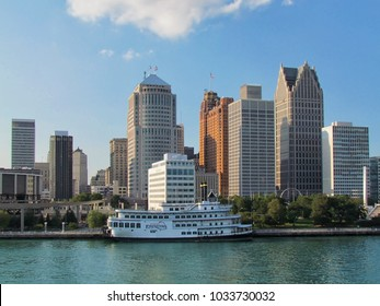 Detroit, USA - August 29, 2012: Detroit city downtown riverfront cityscape viewed across the river from Canada bank on sunny summer day. Detroit Princess riverboat moored to Detroit Riverwalk