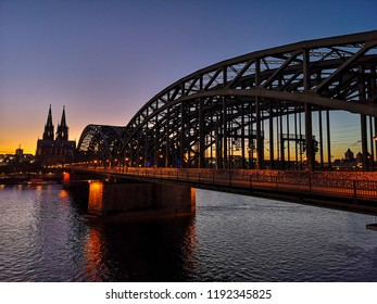 Deutzer bridge over river rhein with cathedral of cologne in the background at sunset with blue sky