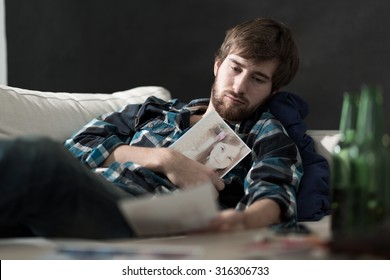 Devastated sad man with a photo of ex girlfriend