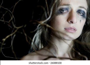 Devastated young woman on black background. Branch next to her face.