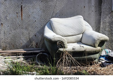 Devastation or crisis symbol. Old crumbling soft chair on the street against a concrete wall with rusty smudges