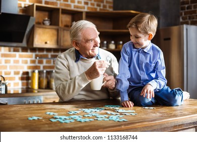 Develop your skills. Joyful elderly man smiling and assembling jigsaw puzzle with his little grandson