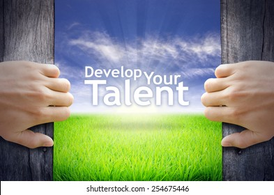 """Develop your Talent"" Motivational quotes. Hands opening a wooden door then found a texts floating among new world as green grass field, Blue sky and the Sunrise."