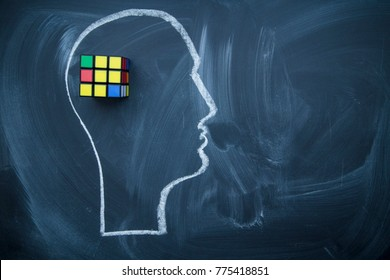 Develope creative thinking. A head drawn with a chalk on a blackboard and a Rubik's Cube. Space for your text or produst display.