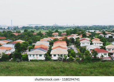 Developed housing area in Bangkok, Thailand, the house's roofs are colorful with grass in foreground