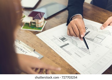 Developer holding and explaining a housing concept to a business woman client for real estate development purposes with a contract agreement proposal next to the floor plans