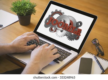 Developer or web designer at work. Close-up top view of man working on laptop with joomla on screen. all screen graphics are made up.