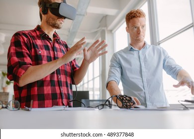 Developers testing an augmented reality device with a broad range of uses from gaming to visual aid. Young man wearing vr headset with coworker working on computer.