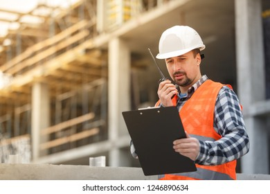 Developing engineer wearing white safety vest and hardhat with walkie talkie and clipboard inspecting construction site. Development and construction industry concept
