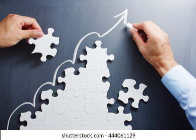 Developing growth strategy. Concept image of management and marketing.  Working on steps shaped jigsaw puzzle. Drawing up arrow on blackboard.