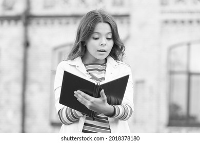 Developing her reading skills. Little girl read book outdoor. Small kid enjoy reading day. Adorable bibliophile. Child imagination. Home reading. School and education. Reading makes her smart