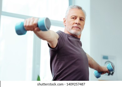 Developing muscles. Strong fit aged man looking at his hand while training with dumbbells