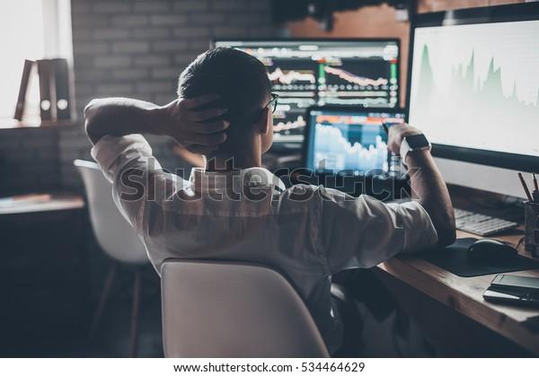 Elaboración de nuevos enfoques. Vista posterior de un joven con ropa informal sosteniendo la mano en la parte trasera de la cabeza y trabajando mientras está sentado en el escritorio en una oficina creativa