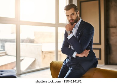 Developing a new idea...Handsome and successful businessman in stylish suit is thinking about something while standing at office