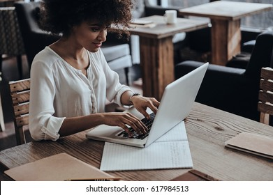 Developing new project. Beautiful young African woman using computer and smiling while sitting in cafe