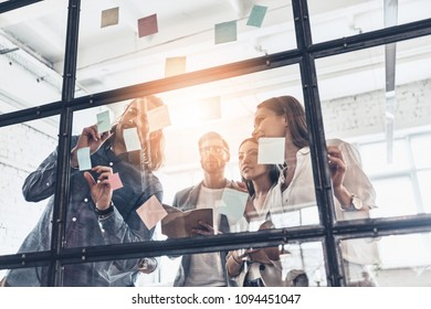 Developing new strategy. Group of young modern people in smart casual wear using adhesive notes while standing behind the glass wall in the board room