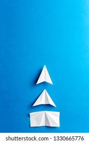 Development attainment, motivation, growth concept. Business concept of goals, success, achievement and challenge. White paper airplanes under construction on blue background.