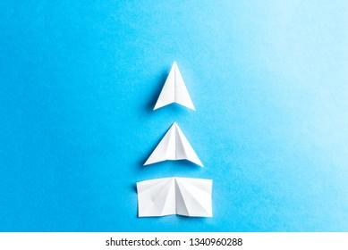 Development attainment, motivation, growth concept. Business concept of goals, success, achievement and challenge. White paper airplanes under construction on blue background. Horizontal composition.