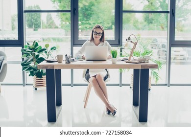 Development, authority, feminity concept. Full length of pretty business woman, sitting at her light modern work station, checking e mails in front of digital device, smiling, in trendy specs