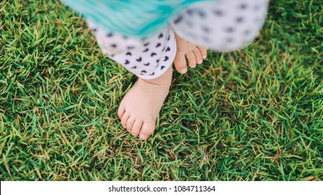Development of baby : first steps of new born, feet of toddler on the green grass.
