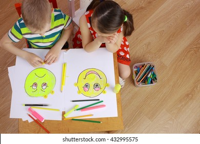 the development of emotional intelligence. child psychology. girl and boy depict different emotions. the girl and the boy draw happy and sad emoticons