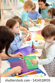 Development learning children in preschool. Children's project in kindergarten. Group of kids and teacher cutting paper and gluing with glue stick on art class in kindergarten or daycare
