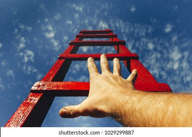 Development Motivation Career Growth Concept. Mans Hand Reaching For Red Ladder Leading To A Blue Sky