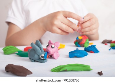 Development of small motor skills of children. Child sculpts from plasticine pig and bunny