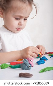Development of small motor skills of children. Girl sculpts from plasticine pig and bunny