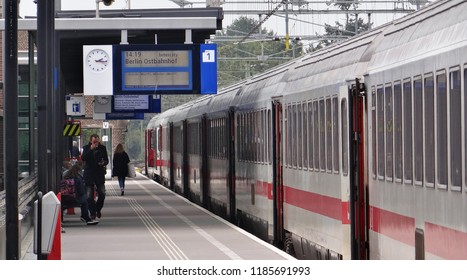 Deventer / Netherlands - September 25 2017: The IC (InterCity) Amsterdam - Berlin at the railroad station of Deventer with german passenger coaches and people boarding at the platform.