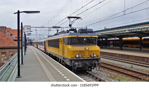 Deventer / Netherlands - September 25 2017: The IC (InterCity) Amsterdam - Berlin at the railroad station of Deventer with a dutch electric locomotive and german passenger coaches