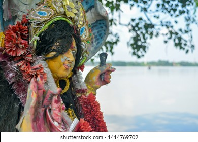 A Devi Maa Durga sadly looks down with tousled hair while tears flow the eyes during Durga Maa visarjan or immersion at Ganga or Ganges river. It reflects the sad moments for all bengali people.