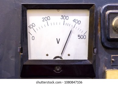 The device is an analog voltmeter vintage in the instrument panel, close-up.