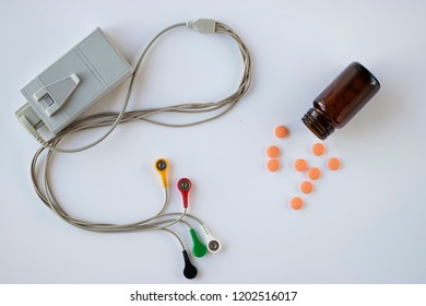 Device of holter monitoring and pills on white background. The concept of diagnosis and treatment of cardiovascular diseases.